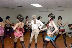 MC y las chicas del Kit Kat Club. Waddys Jaques hace el personaje que realizaran Joel Grey y Alan Cumming.